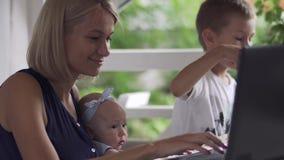 Vrouw met de kinderenwerken aangaande laptop in koffie stock videobeelden