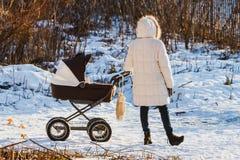 Vrouw met de kinderwagenwinter in openlucht Stock Afbeeldingen