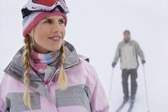 Vrouw met de Mens die op Helling ski?en stock fotografie