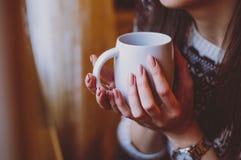 Vrouw met de mooie kop van de manicureholding van koffie in morni royalty-vrije stock foto