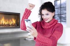 Vrouw met de winterkleren die cellphone thuis gebruiken Stock Afbeeldingen