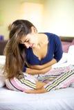 Vrouw met de zieken van het maagprobleem in bed Royalty-vrije Stock Afbeelding