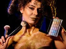 Vrouw met decoratieve schoonheidsmiddelen Het meisje houdt oogschaduw en borstel Stock Afbeelding