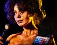 Vrouw met decoratieve schoonheidsmiddelen Het meisje houdt oogschaduw en borstel Stock Foto