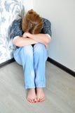 Vrouw met depressiezitting in de hoek van ruimte Royalty-vrije Stock Foto's