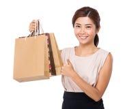 Vrouw met document omhoog zak en duim Royalty-vrije Stock Afbeeldingen