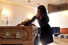 Vrouw met doodskist die bij begrafenis in kerk schreeuwen stock foto