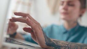 Vrouw met een grote tatoegering bij wapen het typen, mededeling, het werk stock videobeelden