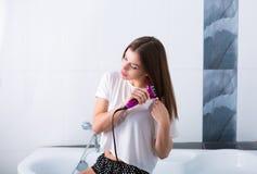 Vrouw met een hete het rechtmaken borstel Royalty-vrije Stock Afbeelding