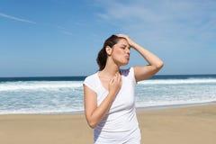 Vrouw met een hoofdpijn op het strand stock afbeelding