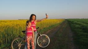 Vrouw met een kind die selfie in aard doen Een gelukkige moeder met haar dochter wordt gefotografeerd in het platteland De fietse stock footage