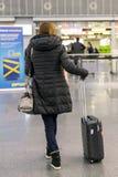 Vrouw met een koffer bij de luchthaven vaas toe stock foto's