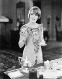 Vrouw met een kop thee en een canapï ¿ ½ in haar handen (Alle afgeschilderde personen leven niet langer en geen landgoed bestaat  royalty-vrije stock afbeelding
