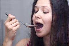 Vrouw met een lepel in een mond Stock Foto