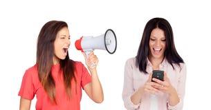 Vrouw met een megafoon die haar vriend met mobiel schreeuwen royalty-vrije stock afbeeldingen