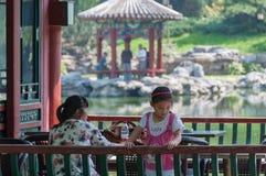 Vrouw met een meisje die in een de zomerhuis ontspannen, een paviljoen in een park royalty-vrije stock foto's