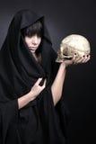 Vrouw met een menselijke schedel in zwarte Stock Afbeeldingen