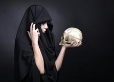 Vrouw met een menselijke schedel in zwarte Royalty-vrije Stock Afbeelding