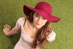 Vrouw met een modieuze hoedenzitting op gras Royalty-vrije Stock Foto's