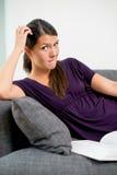 Vrouw met een ontevreden uitdrukkingslezing stock foto's