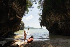 Vrouw met een peddel die zich naast overzeese kajak bij afgezonderd strand in Krabi, Thailand bevindt stock afbeeldingen
