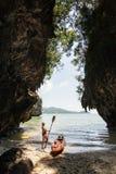 Vrouw met een peddel die zich naast overzeese kajak bij afgezonderd strand in Krabi, Thailand bevindt stock foto