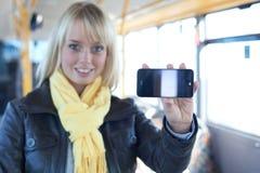 Vrouw met een smartphone binnen een bus Stock Afbeeldingen