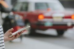 Vrouw met een smartphone die taxi tot cabine of alternatieve wijzen van vervoer opdracht geven Royalty-vrije Stock Foto