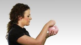 Vrouw met een spaarvarken stock footage