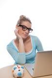 Vrouw met een spaarvarken die op haar laptop onderzoeken Stock Afbeeldingen
