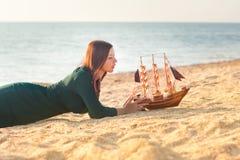 Vrouw met een stuk speelgoed schip Stock Afbeelding