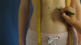 Vrouw met een vlakke buik Close-up op een blauwe achtergrond Gezond voedsel, geschiktheid stock video