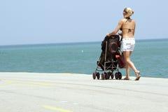 Vrouw met een wandelwagen op strand stock fotografie