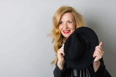 Vrouw met een zwarte hoed op grijs Royalty-vrije Stock Fotografie