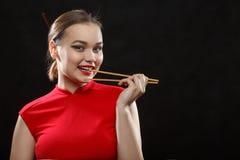 Vrouw met eetstokjes stock afbeelding