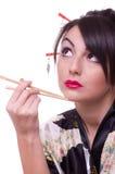 Vrouw met eetstokjes en sushi Royalty-vrije Stock Foto's