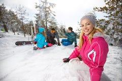 Vrouw met familie die op sneeuw bij het ski?en genieten van Royalty-vrije Stock Foto