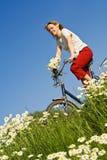 Vrouw met fiets onder de lentebloemen Royalty-vrije Stock Afbeeldingen
