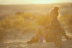 Vrouw met fles van waterzitting op zeekust bij zonsondergang stock foto