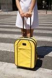 Vrouw met gele koffer op zebrapad Stock Afbeeldingen