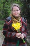 Vrouw met gele narcissen in handen Stock Fotografie