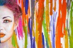 Vrouw met geschilderd gezicht op een gekleurde achtergrond Stock Fotografie
