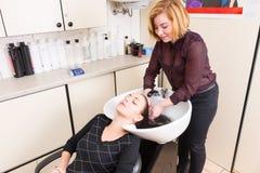 Vrouw met Gesloten die Ogen het Hebben van Haar in Salon wordt gewassen stock fotografie