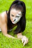 Vrouw met gezichtskunst op gras Stock Fotografie