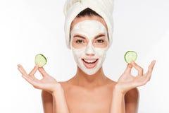 Vrouw met gezichtsmasker en komkommerplakken in haar handen Stock Afbeelding