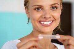 Vrouw met Gezonde Witte Tanden die Tanden gebruiken die Strook witten royalty-vrije stock fotografie