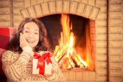 Vrouw met gift dichtbij open haard royalty-vrije stock foto's