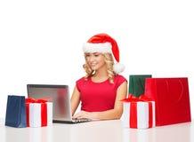 Vrouw met giftdozen, zakken en laptop computer Royalty-vrije Stock Afbeelding
