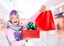 Vrouw met giften na het winkelen aan het nieuwe jaar bij winkel Royalty-vrije Stock Afbeeldingen