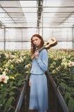 Vrouw met gitaar die zich tussen bloemen bevinden Stock Foto